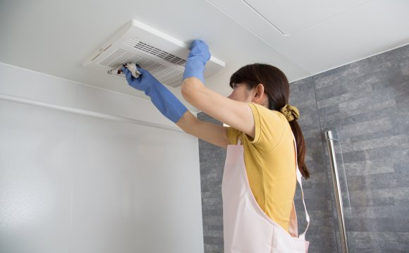 Woman cleaning ventilation
