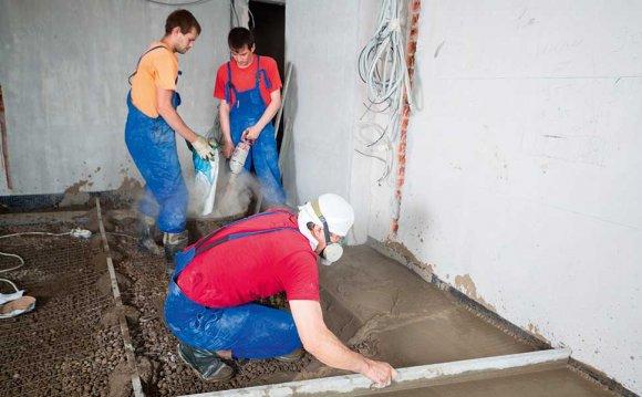 Three workmen pouring a