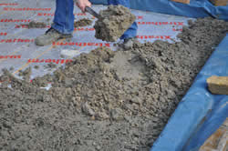 Concrete being spread over base