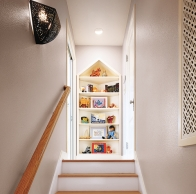 peaked bookshelf creating a focal point at the top of an attic stairway in this refinished attic